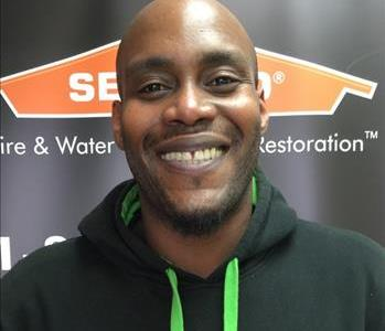 Male employee with dark hair smiling in front of a SERVPRO black banner