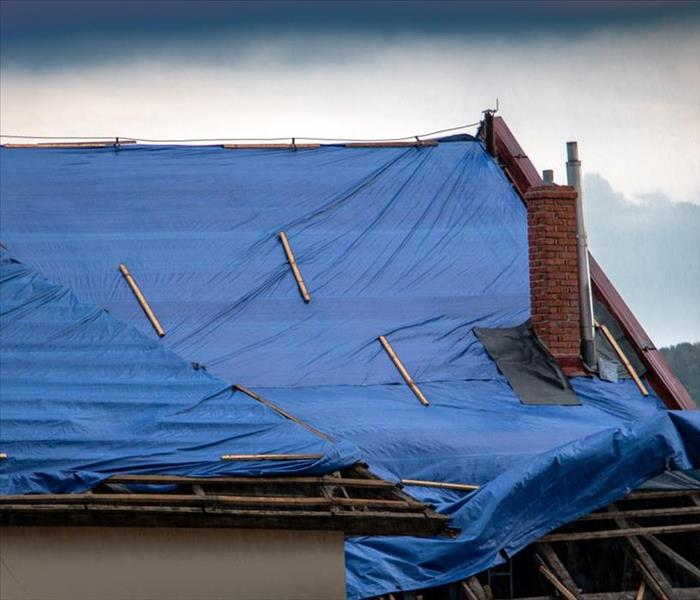 The protective tarpaulin on the roof flutters at the storm with rain.